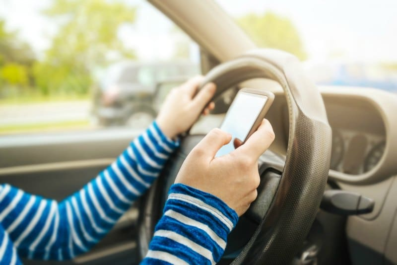 Woman driving car and texting message on smartphone, using mobile phone device while driving, dangerous and risky behavior in traffic