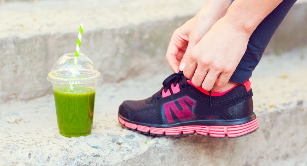 green smoothy on step and person lacing up sneakers