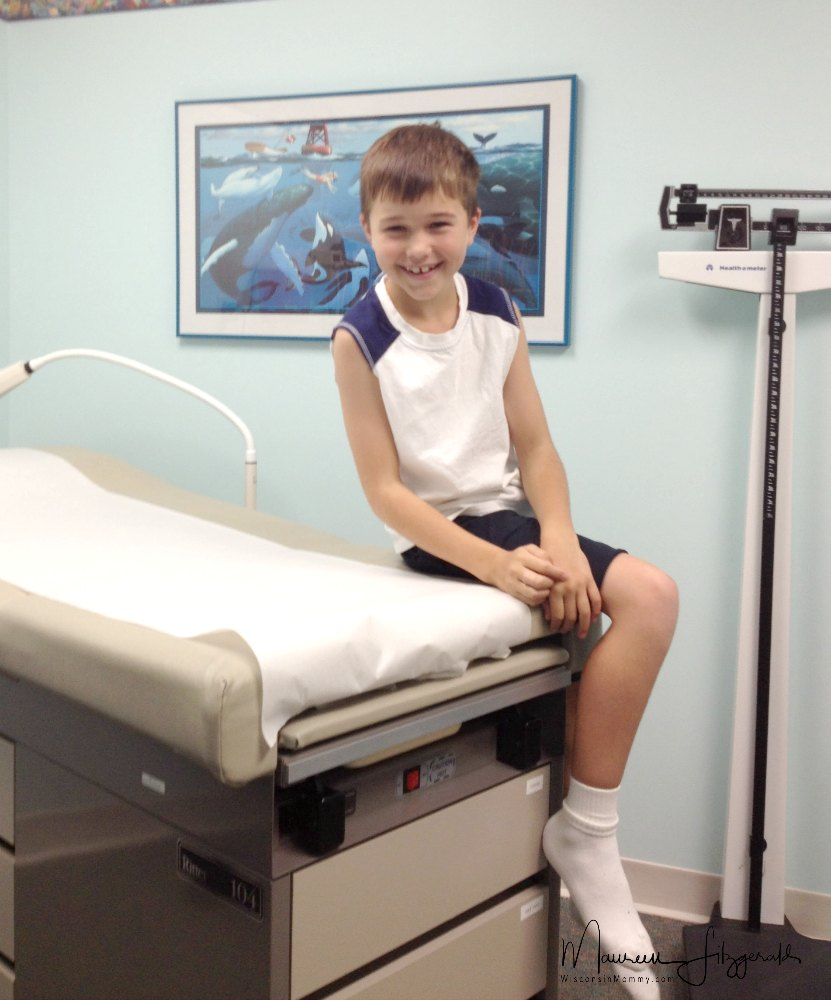 boy sitting on table at doctor's office