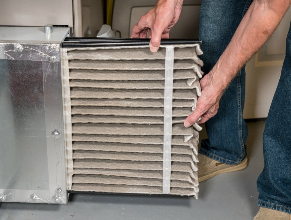 hands pulling out dirty furnace air filter