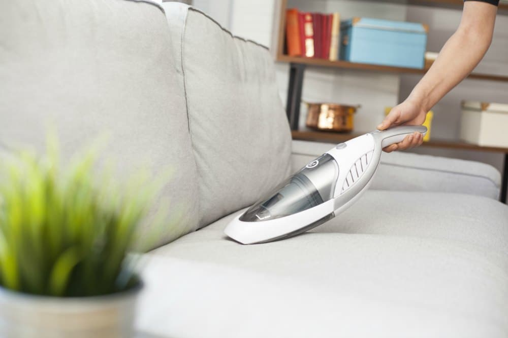dust buster vacuuming white couch