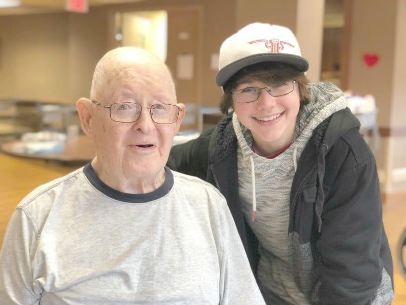 older man and teen smiling at camera