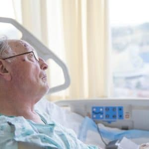 older man in hospital looking out window