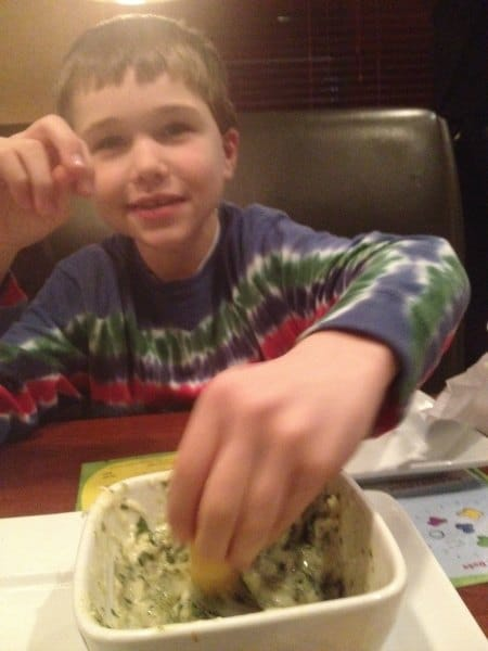 boy scooping spinach dip with chip