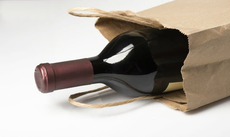 A bottle of red wine in a paper bag, perhaps being given as a gift or bought at a liquor store, on a white background with reflection and shadow