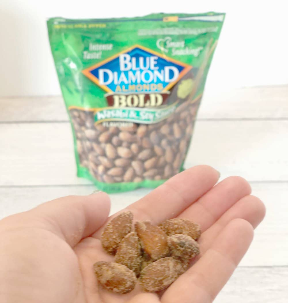 hand holding almonds in front of package