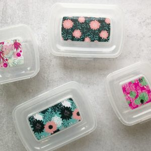 four containers with pretty floral degign on top and attached lids