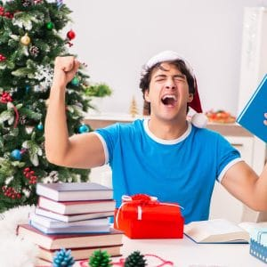 college student opening present in front of tree