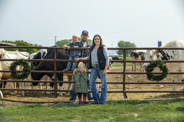 farming family standing in front of fence and cows
