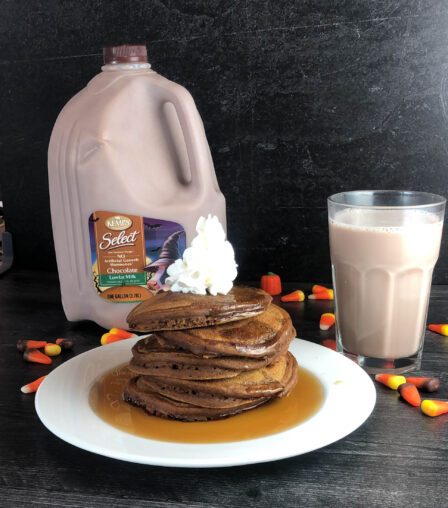 stack of pancakes, gallon of chocolate milk and a glass of milk